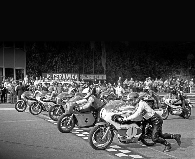 Twenty cylinders on the front row start to fire up for the race: Giacomo Agostini, Yamaha (1), Gianfranco Bonera, MV Agusta (4), Phil Read, MV Agusta (3), Teuvo Länsivuori, Yamaha (2), Barry Sheene, Suzuki (5). On the second row is Armando Toracca, Paton; Victor Palomo, Yamaha and Adu Celso Santos, Yamaha.