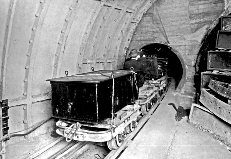 From the archives: Wearing just a trilby as head protection, a Post Office Underground Railway worker enters a tunnel during the line's operational days with a 'freight train' carrying a transformer secured by rope on a flat truck. THE POSTAL MUSEUM