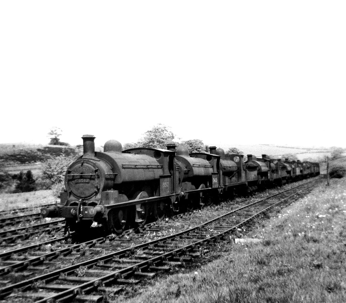 The sight that greeted us as we entered the Royal Ordnance Factory sidings at Heapey on May 16, 1959 – 15-old-steam locomotives dumped in the countryside unwanted and with nowhere to go. Left to right are: Nos. 51512, 51423, 52216, 51415, 52268, 51457, 50647, 51404, 52237, 43890, 51546, 50712, 43984, 51316 and 40178. Most, if not all, will have been to Horwich Works first where they will have been formally condemned before being towed out to Heapey in varying stages of incapacitation to await disposal. The leading four locomotives were among the first to be sent to Heapey. No. 51512 was ex-Gorton from where it had been withdrawn in July 1958. Built by Beyer Peacock in February 1882 it was one of the 0-6-0 tender engines to be converted in January 1899 to a saddle tank. It eventually departed for the Central Wagon Co at Ince near Wigan, possibly being the first BR loco to go there.
