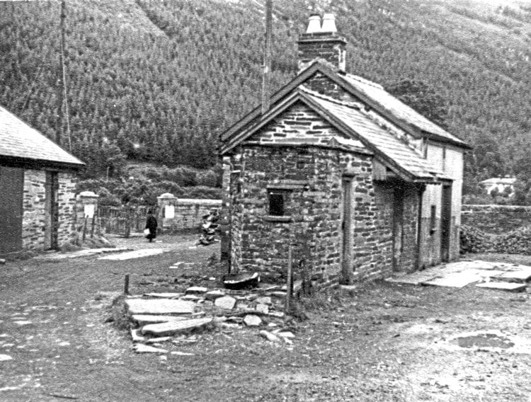 The partly demolished remains of Corris Station, August 30 1950, two years after the railway closed. The station's storm-damaged overall roof had been removed soon after closure. The slate slabs to the right of the buildings are the remains of the passenger platform that sat beneath the roof; those in front of the building were a crude stop block for the siding that once ended here and was connected to the passing loop to the left of the main building. For a few years these sad remains were used by the local coal merchant – piles of coal can be seen on the site of the carriage shed. The station buildings were finally demolished in the summer of 1968, but the railway's former stables, on the left, now form the small but excellent Corris Railway Museum.