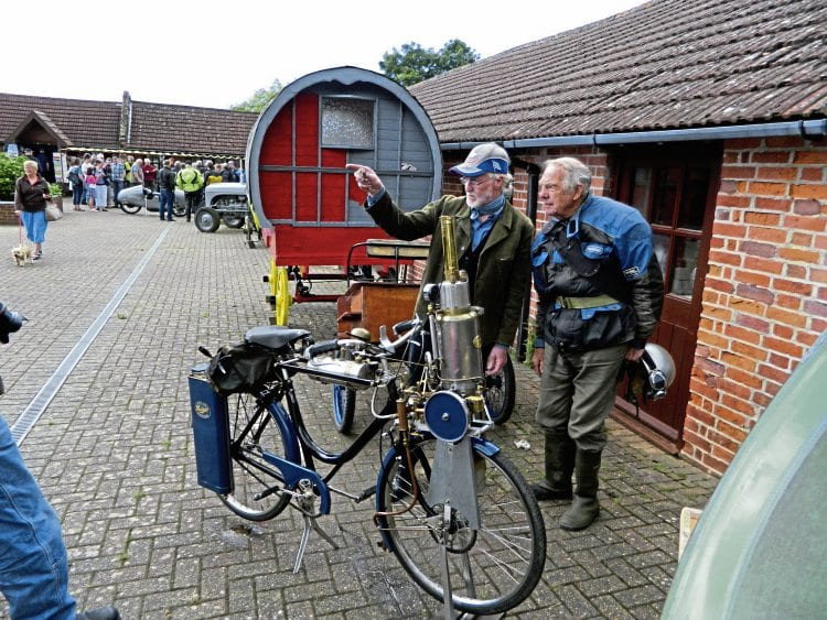 An interesting conversation takes place beside the Hudspith steam bicycle.
