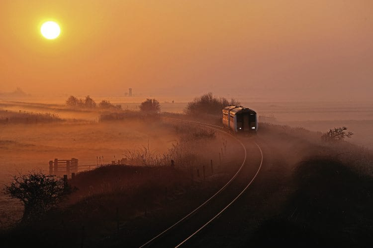 WHERRY DAWN: Low sun and misty fields combine to great effect as a Greater Anglia Class 156 heads towards Acle, Norfolk, with a Great Yarmouth to Norwich service on March 12, 2014. Steve Arthur