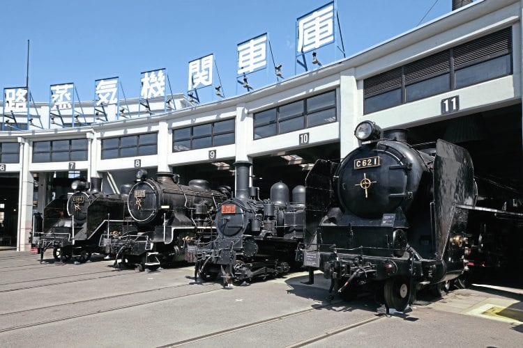 Four locos outside the historic Umekoji roundhouse. From right to left: powerful 4-6-4 C62 1, built by Hitachi in 1948, and 4-4-2T Number 1080, built in Scotland by Dubs in 1901 as a 4-4-0 tender loco (rebuilt in 1926 to the current 4-4-2T design). Nearer the camera are two Kawasaki-built locos, 2-8-0 9633 (right), dating from 1914, and (left) 1935 vintage 2-6-4T C11 64. Between 1932 and 1947, 381 C11s were built. Fifty have been preserved, including five that are currently in working order. JAMES WAITE